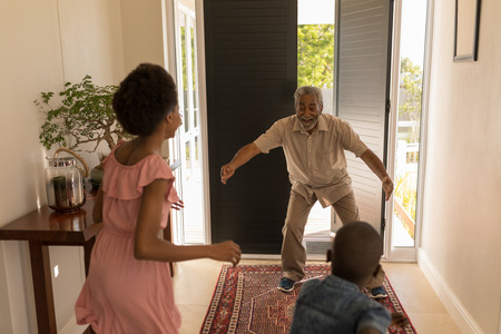 Front view of a happy proud African American grandfather got excited after seeing his grandchildren at home 写真素材