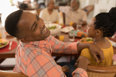Rear view of African American happy couple having fun while sitting at the dining table with their family at home Standard-Bild