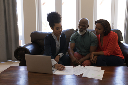Front view of a female real estate agent and a senior couple discussing over documents while sitting on the sofa in living room at home