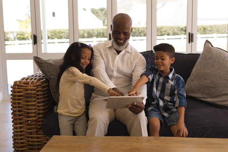 Front view of a happy multi-generation African American family using digital tablet in living room at home