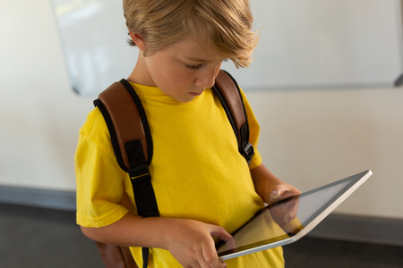 Front view of Caucasian boy with school bag using digital tablet in a classroom at elementary school Фото со стока