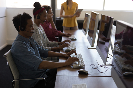 Side view of diverse team of call centre agents working on personal computer while talking on headset in modern office Imagens