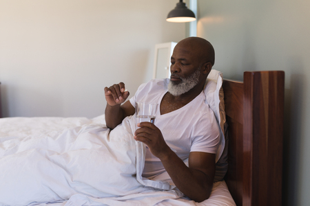 Front view of senior African American man taking medicating with a glass of water in bedroom at home