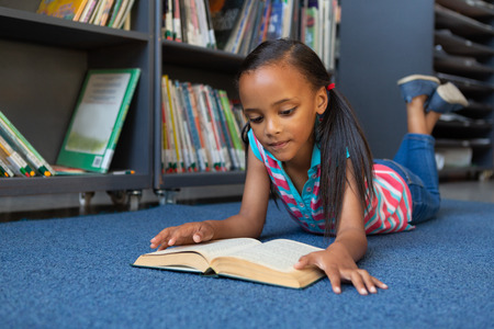Front view of a cute mixed-race schoolgirl reading a book while lying down in the library at school