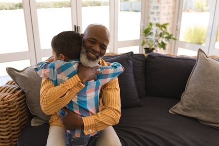 Front view of proud African American grandfather and grandson embracing each other in living room at home