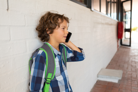 Side view of a Caucasian schoolboy talking on mobile phone while leaning against a wall in the corridor at school