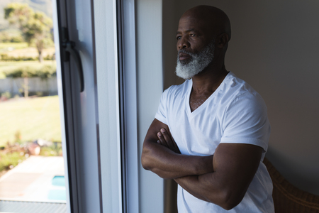 Front view of a thoughtful senior African American man looking through window with crossed arms at home
