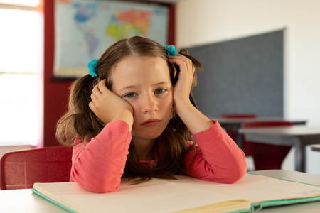 Front view of sad Caucasian girl leaning on desk in a classroom at elementary school