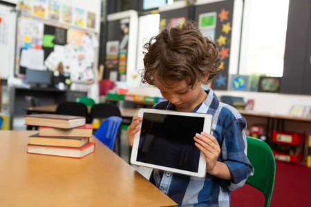 Front view of a Caucasian schoolboy holding digital tablet in front of him and looking at it in the library at school Stok Fotoğraf