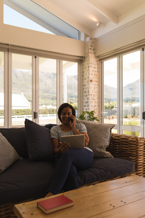 Front view of woman talking on mobile phone while using digital tablet in living room at home