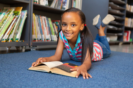 Front view of a happy mixed-race schoolgirl reading a book while lying on the ground in the library at school
