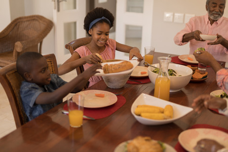 Side view of  African American multi-generation family having meal together on dining table at home
