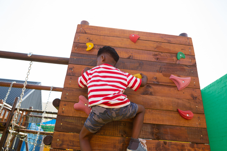 Rear view of African-American schoolboy climbing a wall in the school playground on a sunny day