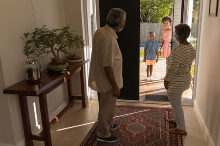 Front view of African American grandparents standing near door and inviting their grandchildren into their home