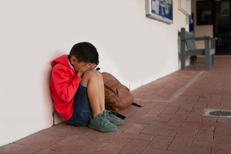 Side view of sad mixed-race schoolboy sitting alone with hands covering his face on floor in corridor at elementary school