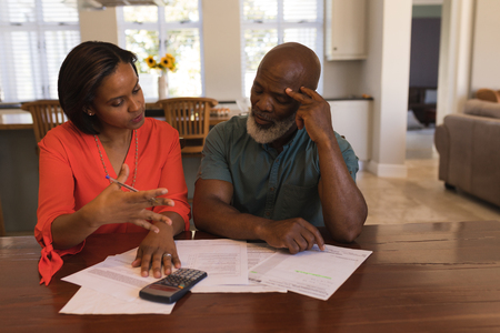 Front view of an active senior couple discussing over invoices in the living room at home Imagens