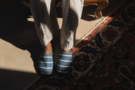 Low section of senior African American man wearing slippers and relaxing at home