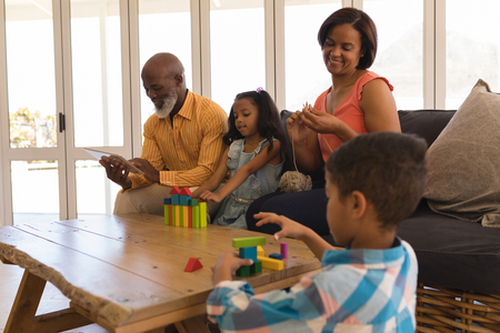 Front view of African American multi-generation family enjoying their free time in living room at home