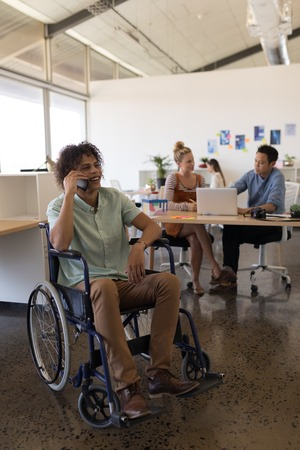 Front view of handsome disabled male executive talking on mobile phone in office with coworkers in the background