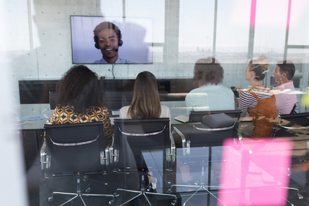 Rear view of multi-ethnic business team attending video call with African-american oversees colleague in a conference room at modern office Banque d'images - 121801651