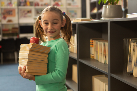 Side view of smiling Caucasian schoolgirl with books and apple standing in library at elementary school Stok Fotoğraf