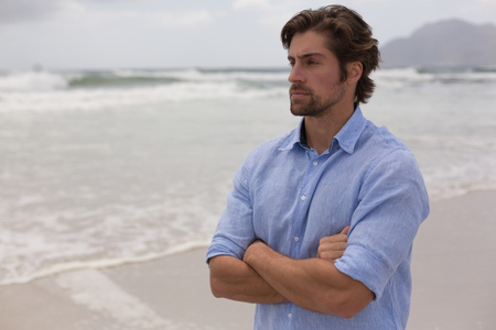 Side view of a thoughtful man standing with arms crossed on the beach next to the waves Stockfoto