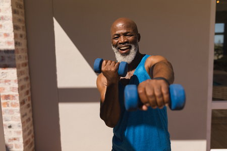 Front view of active senior African American man training arms with dumbbells in the backyard of home