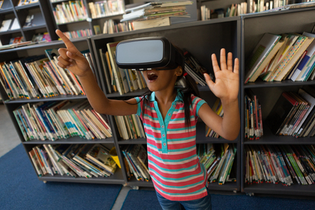 Front view of playful mixed-race schoolgirl using virtual reality headset in the library at school Stok Fotoğraf