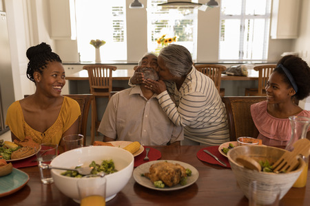 Front view of African American senior woman kissing her husband surrounded by his daughter and his grand daughter at the dining table at home 写真素材