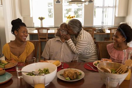 Vorderansicht einer afroamerikanischen Seniorin, die ihren Mann küsst, umgeben von seiner Tochter und seiner Enkelin am Esstisch zu Hause Standard-Bild