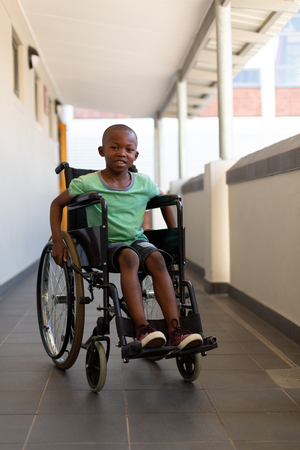 Front view of a African American disabled schoolboy looking at camera while sitting in a wheelchair in corridor at elementary school