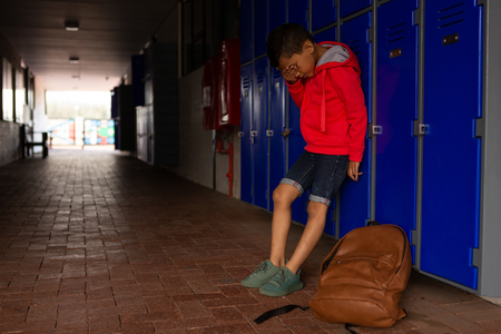 Side view of sad mixed-race schoolboy standing alone covering his face with his hand in corridor at elementary school