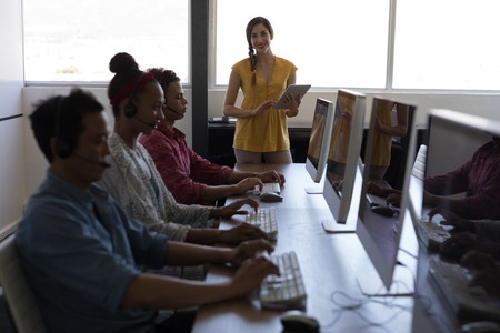 Front view of mixed-race female executive using digital tablet while coworkers talking on headset in office Banco de Imagens