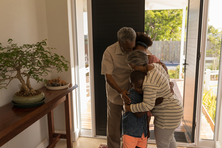 Front view of happy African American grandparents embracing their grandchildren at home