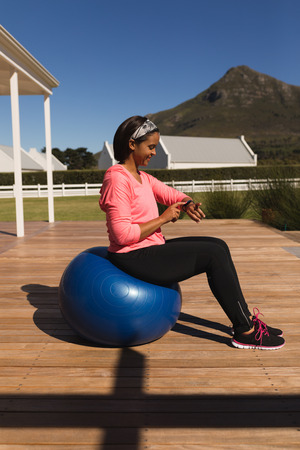 Side view of middle-aged African American woman using smartwatch while sitting on an exercise ball in the backyard of home