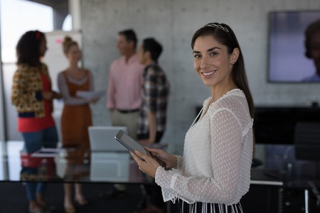 Portrait of attractive Caucasian female executive smiling while using digital tablet in office with business team talking in the background Banque d'images