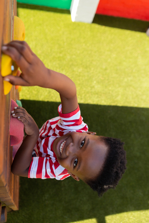 High angle view of a smiling African American schoolboy climbing a wall in the school playground on a sunny day 写真素材 - 121812316