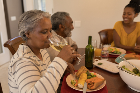 Side view of a multi-generation African American family eating dinner together on dining table at home. Grandmother is drinking a glass of white wine. Stock Photo