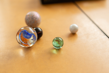 Close-up of beautiful marbles on a wooden desk in classroom at school Imagens