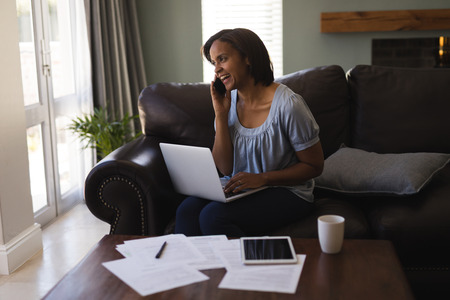 Front view of woman talking on mobile phone while using laptop in living room at home Stock Photo