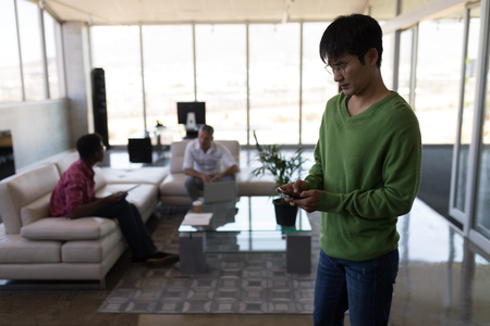 Front view of Asian male executive using mobile phone in modern office while diverse coworkers are interacting on couch
