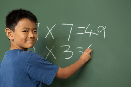 Front view of an Asian schoolboy doing math on greenboard in a classroom at elementary school