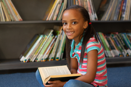 Front view of a happy mixed-race schoolgirl reading a book in the library at school