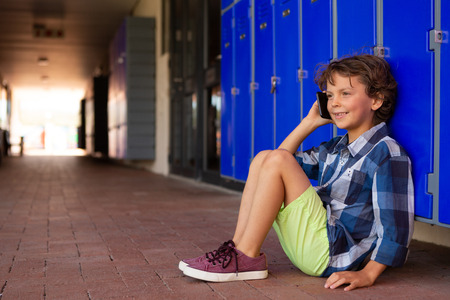 Front view of a cute smiling Caucasian schoolboy talking on mobile phone while sitting in the corridor at school Stock Photo