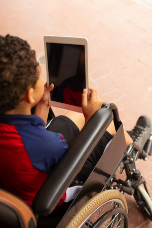 High angle view of cute mixed-race disabled schoolboy using digital tablet in corridor at elementary school