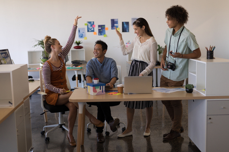 Front view of casually dressed multi-ethnic business colleagues interacting with each other and smiling in modern office