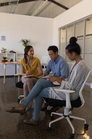 Vista laterale di diversi colleghi di lavoro che discutono di piani mentre scrivono su un diario in un ufficio moderno