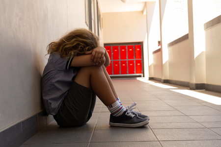 Side view of mixed -race sad schoolgirl sitting on the floor with his head down in the school corridor Stock Photo