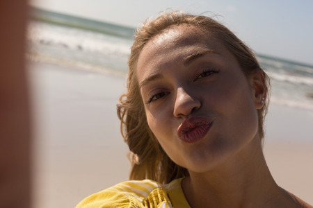 Selfie of a beautiful woman having fun and standing at beach on a sunny day Standard-Bild - 121812741