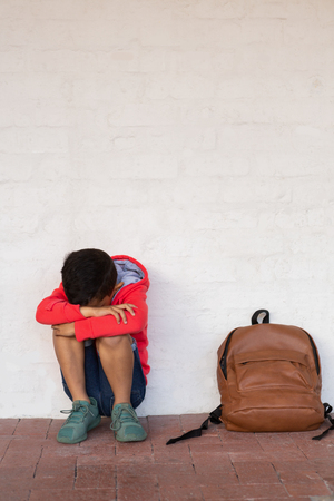 Front view of sad mixed-race schoolboy sitting alone with his bag pack next to him on floor in corridor at elementary school Stock Photo